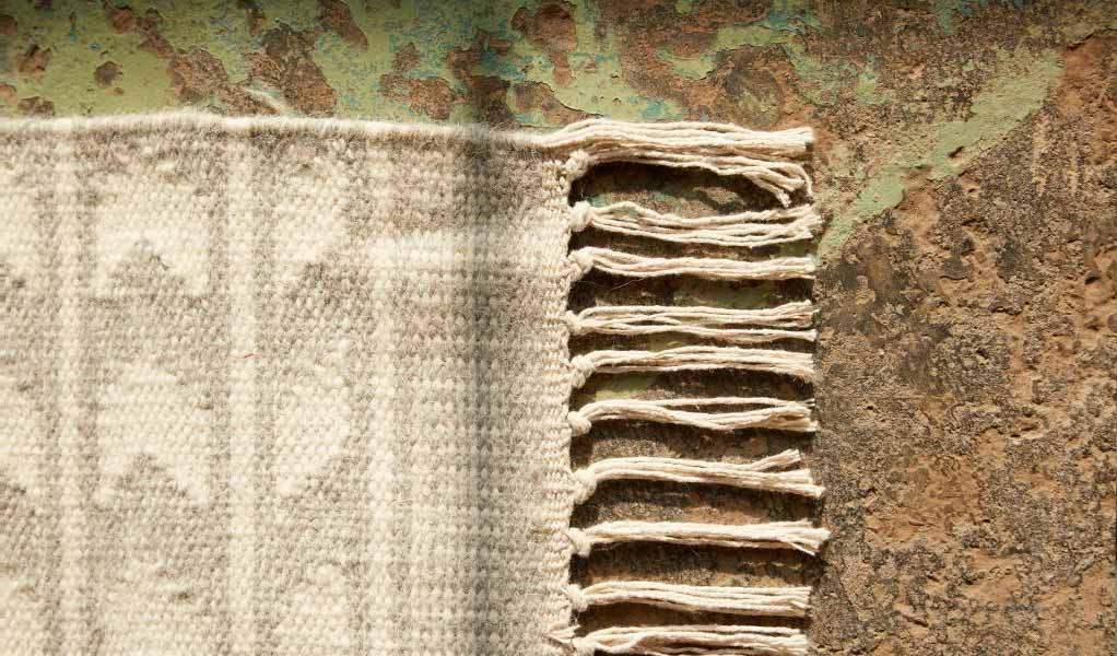 The corner of a handwoven rug with a fringe detail, subtle pattern, and nautral colors.