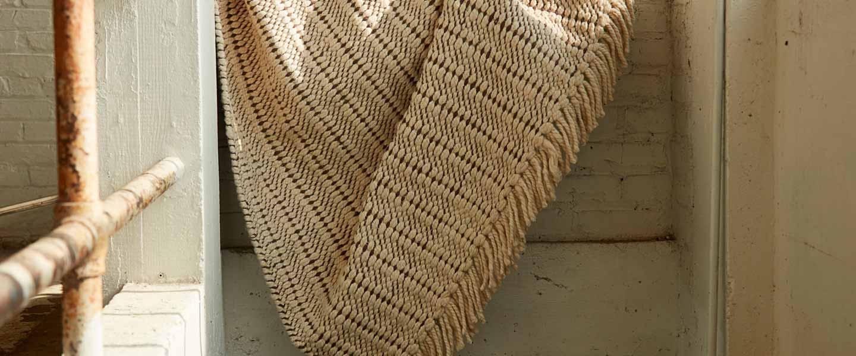 A cream-colored, handwoven rug hangs on a stair rail.